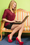 Fashion woman sitting on sofa using pc laptop Stock Photo