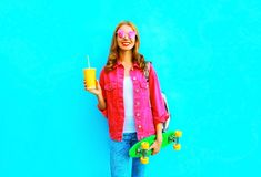 Fashion woman with skateboard, cup of fruit juice in pink denim jacket Royalty Free Stock Images