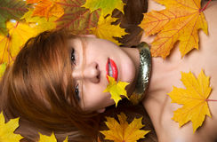 Fashion woman smiling joyful holding autumn yellow maple leaf in Stock Image