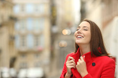 Fashion woman in the street breathing in winter. Fashion happy woman wearing a red coat in the street breathing in winter royalty free stock images