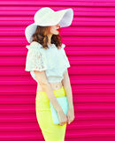 Fashion woman in summer straw hat with handbag clutch over colorful pink Stock Images