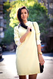Fashion woman with the sun in the back. Fashion woman with the sun in the back wearing an yellow dress royalty free stock photo