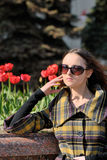 Fashion woman in sun glasses. Young woman stands in sun glasses, some blurred tulips on background Royalty Free Stock Photo