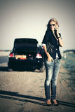 Fashion woman in sunglasses calling on phone next to broken car Royalty Free Stock Images