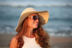 Fashion woman with sunglasses and hat smiling on sunny day at sea Royalty Free Stock Photography