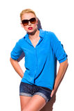 Fashion woman in sunglasses is leaning on the wall. Young woman in sunglasses is leaning on the wall and looking at camera. Three quarter length studio shot Royalty Free Stock Images