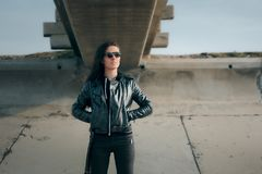 Fashion Woman with Sunglasses and Leather Jacket Rock Biker Style. Rocker tomboy female model in fashionable edgy outfit royalty free stock photos