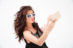 Fashion woman in sunglasses making selfie photo on smartphone. Isolated on a white background stock photography