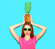 Fashion woman in sunglasses with pineapple on head over blue. Background Stock Photography