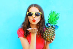 Fashion woman in sunglasses with pineapple sends an air kiss over colorful blue. Background Stock Image