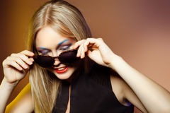 Fashion woman in sunglasses, studio shot. Professional makeup. Close-up portrait of beautiful and fashion woman in sunglasses, studio shot. Professional makeup Stock Image