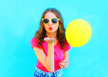 Fashion woman in sunglasses with yellow air balloon sends an air kiss over colorful blue. Background Stock Photos