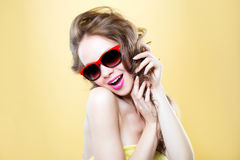 Fashion woman In sunglasses. Fashion woman In sunglasses on a yellow background Royalty Free Stock Photos
