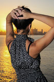 Fashion woman at sunset. Fashion woman with hands on the head staring at horizon by the sea - havana skyline background Stock Image