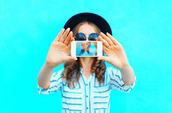 Fashion woman is taking photo self portrait on a smartphone in the city closeup screen over colorful blue. Background Stock Image