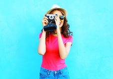 Fashion woman taking picture wearing straw summer hat, sunglasses and vintage camera over colorful blue Royalty Free Stock Photo