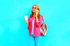 Fashion woman talks on a smartphone in pink denim jacket. Fashion smiling woman talks on a smartphone in a pink denim jacket on blue background Royalty Free Stock Photography