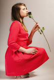 Fashion woman teen girl in red gown with dry rose. Royalty Free Stock Image