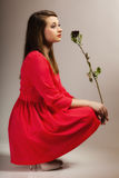 Fashion woman teen girl in red gown with dry rose. Royalty Free Stock Images