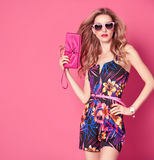 Fashion woman in Trendy Spring Summer Flower Dress. Fashion woman in Trendy Spring Summer Dress. Stylish wavy hairstyle, fashion Sunglasses, Summer Floral Outfit Stock Photo