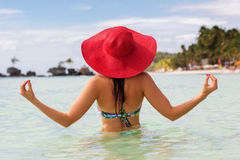 Fashion woman in tropical paradise. Back view of fashion woman is doing meditation on the beach and wearing red hat, summer vacations Royalty Free Stock Photos