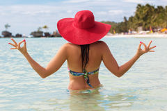 Fashion woman in tropical paradise doing meditation. Back view of fashion woman is doing meditation on the beach and wearing red hat, summer vacations Royalty Free Stock Images