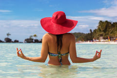 Fashion woman in tropical paradise doing meditation. Back view of fashion woman is doing meditation on the beach and wearing red hat, summer vacations Stock Image