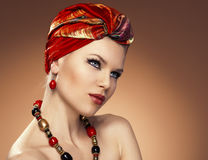 Fashion woman in turban. Beauty fashionable woman with hairs wrapped in turban. Pretty Caucasian model wearing red earrings and necklace posing in studio Stock Photography