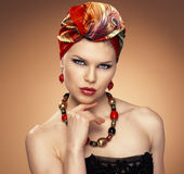 Fashion woman in turban. Close-up portrait of beautiful blue eyed woman with ethnic hairstyle wearing nice jewelery. African styled model with red silk turban Royalty Free Stock Image