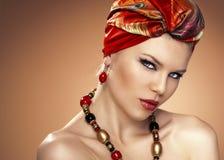 Fashion woman in turban. Fashion portrait of beautiful Caucasian woman wearing turban. African styled model posing in studio Royalty Free Stock Images