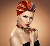 Fashion woman in turban. Pretty fashion girl in turban wearing red earrings, touching her necklace. Beautiful Caucasian blue eyed model with ethnic make-up and Stock Images