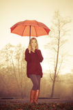 Fashion woman with umbrella relaxing in fall park. Stock Photography