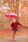 Fashion woman with umbrella relaxing in fall park. Royalty Free Stock Images