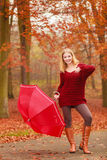 Fashion woman with umbrella relaxing in fall park. Royalty Free Stock Photos