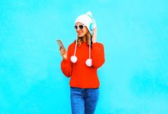 Fashion woman uses smartphone listens to music in wireless headphones in red sweater. On blue background Stock Photography