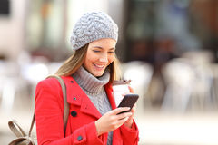 Fashion woman using a phone in winter. Happy fashion woman using a smart phone and holding a take away coffee in the street in winter Stock Photo
