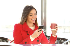 Fashion woman using a smartphone in a coffee shop. Fashion happy woman using a smartphone in a coffee shop and holding a cup ready to drink Royalty Free Stock Photo