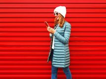 Fashion woman is using smartphone on red background, walking i Stock Image