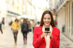 Fashion woman using a smartphone in winter. Front view of a fashion woman wearing red coat using a smartphone in winter and walking towards camera Royalty Free Stock Photo