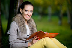Fashion woman using a tablet computer outside in evening park Stock Photo