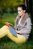 Fashion woman using a tablet computer outside in evening park Stock Photos