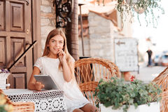 Fashion woman using tablet and sitting by the table. Stock Photo