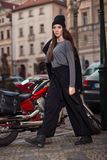 Fashion woman walking in the city near motorbike wearing black hat Royalty Free Stock Photos
