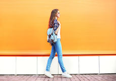 Fashion woman walking in city over colorful orange royalty free stock images