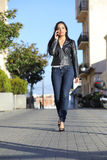 Fashion woman walking on the street talking on the mobile phone. Front view of a fashion woman walking on the street talking on the mobile phone Stock Image
