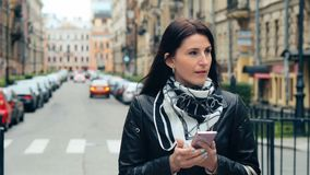 Fashion woman walking and using a smart phone on a city street.  stock footage