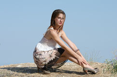 Fashion woman wear dress pose at the edge of a hill Royalty Free Stock Photos