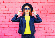 Fashion woman wearing a black hat and yellow knitted sweate rjacket over colorful pink bricks. Background Royalty Free Stock Photo