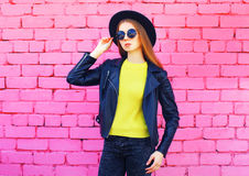 Fashion woman wearing black hat and yellow knitted sweater jacket over colorful pink bricks. Background Royalty Free Stock Photo