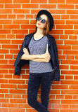 Fashion woman wearing a black rock style over bricks background Royalty Free Stock Photos